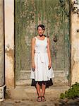 Italy, Ravello, Mature woman wearing white dress posing outside green door
