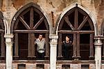Italy, Venice, Couple standing in arcade