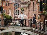 Italy, Venice, Romantic couple walking on footbridge over canal