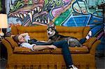 Junger Mann mit Hund, Graffiti im Hintergrund auf dem Sofa schlafen, USA, Utah, Salt Lake City