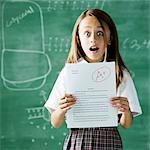 jeune fille dans une salle de classe devant un tableau noir avec un un papier plu