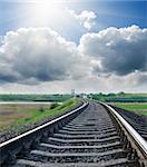 railway to horizon under cloudy sky