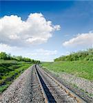 railway goes to horizon in green landscape