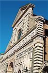 Facade of Church of Santa Maria Novella in Florence against a vivid blue sky.