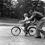 1960ER JAHREN VATER SOHN GEBEN ON BIKE EIN PUSH, LEHRT IHN, WIE MAN FAHRRAD FÄHRT
