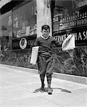 1930s NEWSBOY IN KNICKERS WALKING DOWN STREET HAWKING PAPERS