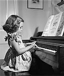 1950s LITTLE GIRL PRACTICING PIANO INDOOR