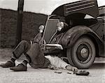 1930ER JAHRE MANN AUF DEM RÜCKEN TRAGEN GESTREIFTE SOCKEN FIXIEREN AUTO
