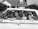 ANNÉES 1960 SOURIANT FAMILLE PÈRE MÈRE FILLE FILS ASSIS DANS VOITURE DEVANT LA MAISON DE BANLIEUE CÔTÉ DÉCOUVRE À L'EXTÉRIEUR