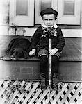 1890S 1900S 1800S WENDE DES JAHRHUNDERTS SAD BOY HALTEN STICK SITTING ON VERANDA NEBEN HUND