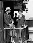 1930ER JAHRE FAMILIE MIT DREI STEHEN AN DER SCHWELLE DER RELING HINTEN ZUG AUTO MIT TRÄGER IM HINTERGRUND