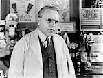 1930s 1940s DRUG STORE SODA FOUNTAIN MAN PHARMACIST WEARING WHITE COAT AND GLASSES LISTENING