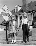 ANNÉES 1960 GARÇON & FILLE HABILLÉ POUR L'ÉCOLE TRANSPORTANT DES BOÎTES À LUNCH PLAID MAIN DANS LA MAIN WATCH ENFANTS SIGNE EN ATTENTE