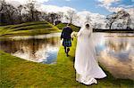 Couple de jeunes mariés marchant sur le pont herbeux