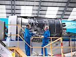 Travailleurs examinant la machinerie de l'avion