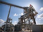 Worker standing on conveyor in quarry