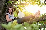 Femme souriante, à l'aide d'ordinateur portable dans l'arborescence