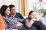 Familie entspannend auf Sofa im Wohnzimmer
