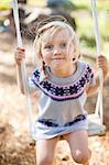 Porträt des kleinen Mädchens auf Seilschaukel im Hinterhof