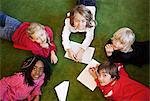 Portrait of multi ethnic school children lying on carpet