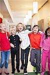 Portrait of happy friends walking in school corridor