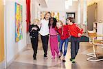 Happy children walking in school corridor
