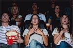 Public dans la salle de cinéma avec des expressions choquées