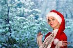 Femme portant le bonnet de Noël, une scène hivernale en arrière-plan, portrait