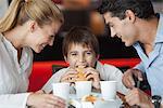 Junge Hamburger mit seinen Eltern in Fast-Food-Restaurant Essen
