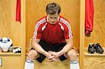 Soccer player sitting alone in locker room