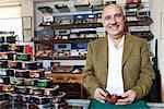 Porträt von glücklich Reife Tabak-Shop-Betreiber mit Dosen auf dem display