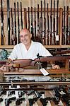 Portrait of happy mature owner of gun shop