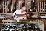 Ausgereifte Waffe Shopbetreiber betrachten Gewehr im Speicher