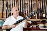 Ausgereifte Waffe-Shop-Besitzer, die Waffe im Shop betrachten