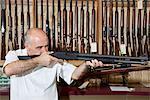 Mature gun shop merchant with rifle aiming