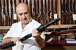 Mature gun shop merchant looking at rifle in store