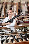 Glücklicher reifer Mann mit Gewehr Pistole speichern