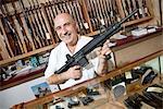 Portrait d'un marchand mature heureux avec fusil en armurerie
