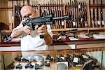 Mature merchant aiming with rifle in gun shop