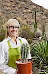 Portrait d'un jardinier principal holding plante de cactus en pot