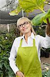 Jardinier heureux hauts femme debout à effet de serre tout en regardant loin