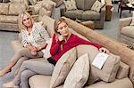 Mutter und Tochter beim Betrachten Preisschild im Möbelhaus auf Sofa sitzen