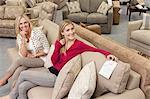 Porträt der glücklichen Mutter und Tochter sitzen auf dem Sofa im Möbelhaus
