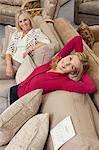 Porträt von Tochter entspannend auf Sofa während Mutter suchen, im Möbelhaus