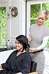 Belle femme heureuse obtenir une coupe de cheveux d'une coiffeuse mature dans le salon de beauté