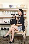Portrait of a mid adult woman showing designer handbag in footwear store