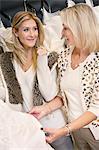 Glückliche Mutter und Tochter schauen einander während der Auswahl Hochzeitskleid in Hochzeits-boutique
