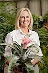 Portrait d'une femme blonde haute heureuse dans le jardin botanique