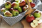 Un panier de pommes biologiques et pommes en tranches sur une planche