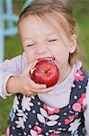 Une jeune fille de mordre dans une pomme